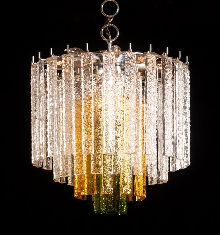 Amazing Murano Venini chandelier. This wonderful lamp consists of a metal frame with 24 clear, 12 amber and six green Murano glass items. It is in a beautiful and working condition. Period 1960s Dimensions: H 55 cm, ø 50 cm.