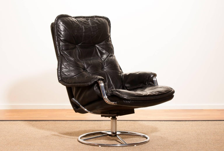 Beautiful lounge chair made in Sweden. This very nice design chair has a black leather seating and armrests on a swivel chrome steel frame. It is in a wonderful condition. Period 1970s Dimensions: H 94 cm x W 68 cm x D 72 cm x Sh 40.