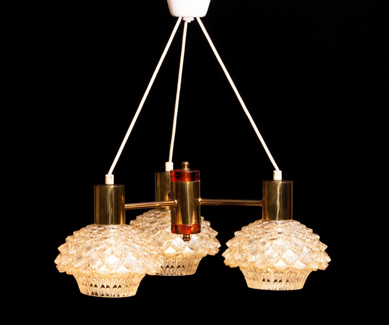 Beautiful chandelier designed by Carl Fagerlund for Orrefors, Sweden. This lamp has three brass arms with amazing glass shades. In the middle a brass cylinder with on the top and bottom an amber glass element. It is in a very nice