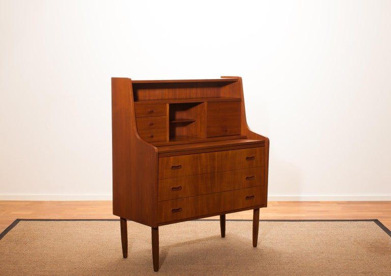 Beautiful secretaire or dressing table in the style of Peter Hvind. The secretaire is made of teak and has a lot of storage space, an extendable writing space and a mirror. It is in wonderful condition. Period 1950s. Dimensions: H 110 cm (height