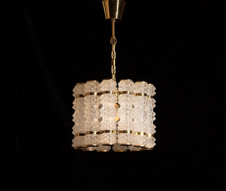Beautiful and in perfect condition brass chandelier or pendant with twelve crystal cylinders.