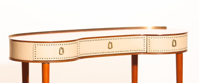 Mahogany/brass and vinyl dressing table or vanity on high legs designed by Halvdan Pettersson in the 1950s for Tibro Möbelfabrik Sweden. This dressing table is in good condition.  Period: 1950s The dimensions are: Total height 69.5 cm - 27.2