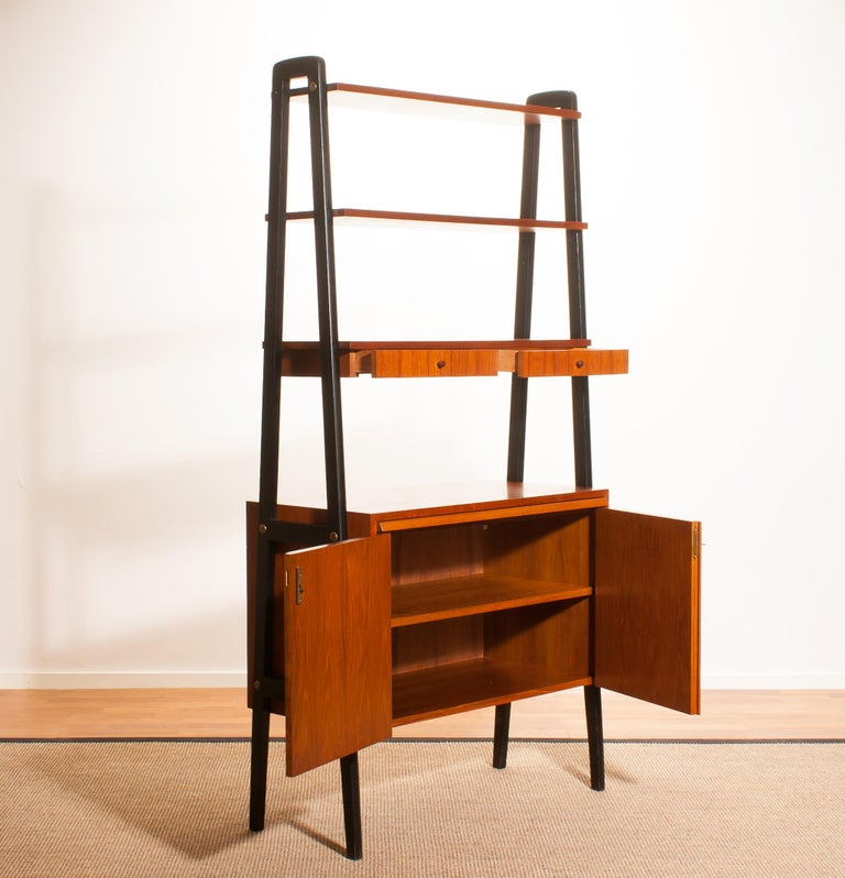 Beautiful cabinet, room divider, bookcase, secretaire in teak with black stands. This cabinet has got two shelves, one shelve with two drawers, two doors and slide-able writing space. It is in a very beautiful condition. Period
