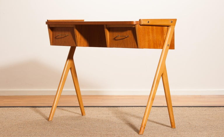 Very beautiful ladies desk from Sweden The table is made of teak and has two drawers with brass details. It is in a very nice condition. Period 1950s. Dimensions: H 70 cm, W 84 cm, D 40 cm.