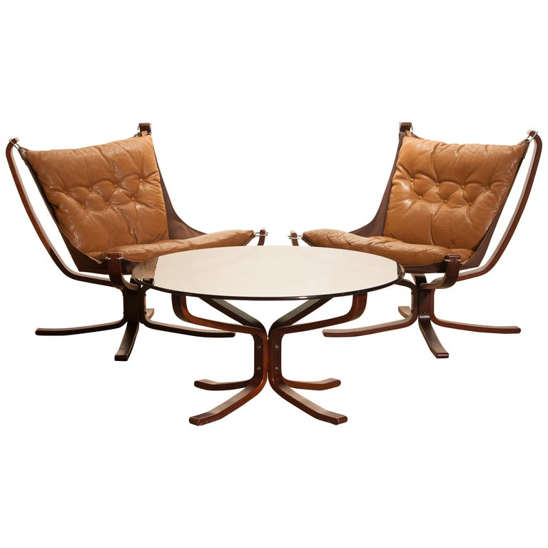 Extremely beautiful set of two 'Falcon' lounge / easy chairs complete with the original coffee table designed by Sigurd Ressell Norway. The chairs and the table are in very good original condition. The camel leather seating as the wooden frames