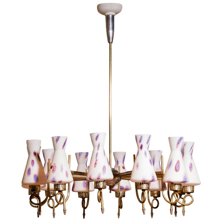 Magnificent large chandelier. This lamp is made of a beautiful brass with polished aluminium shape with twelve white designed Murano glass shades. The shades are labelled. It is in an excellent working condition. Period 1940s. Dimensions: H 90