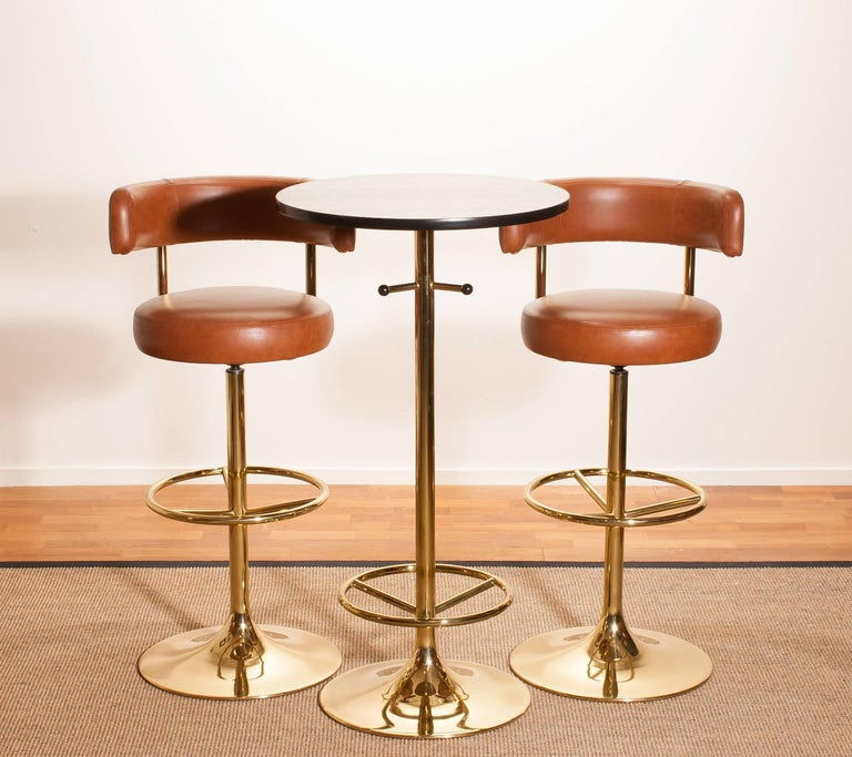 A magnificent set of beautiful bar stools and bar table designed by Börje Johanson for Johanson Design, Sweden. The stools are very comfortable and look great with the combination of brass with new reupholstered cognac faux leather. And also the