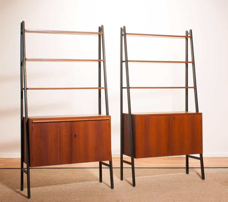 Two beautiful cabinets made of teak with black stands. Because the cupboard is pretty slim and open of form it is also very suitable to use it as a room divider. Each cabinet contain three shelves and a two-door cabinet. One of the cabinets has an