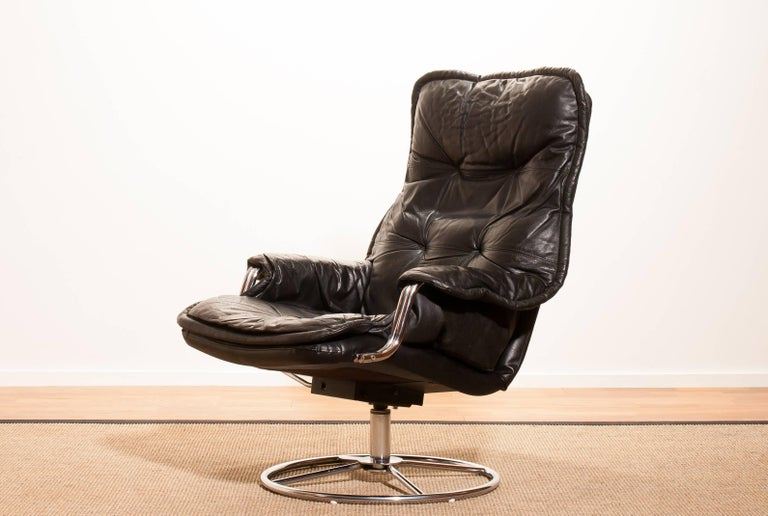 Beautiful lounge chair made in Sweden. This very nice design chair has a black leather seating and armrests on a swivel chrome steel frame. It is in a wonderful condition. Period 1970s Dimensions : H 94 cm , W 68 cm , D 72 cm , Sh 40.