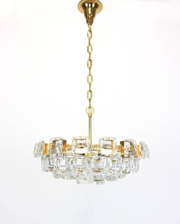 A stunning chandelier by Palwa (Palme and Walter), Germany, manufactured in 1960s. It's composed of jewel-like glass pieces and brass plates with a Brutalist relief.  High quality and in very good condition. Cleaned, well-wired and ready to use.