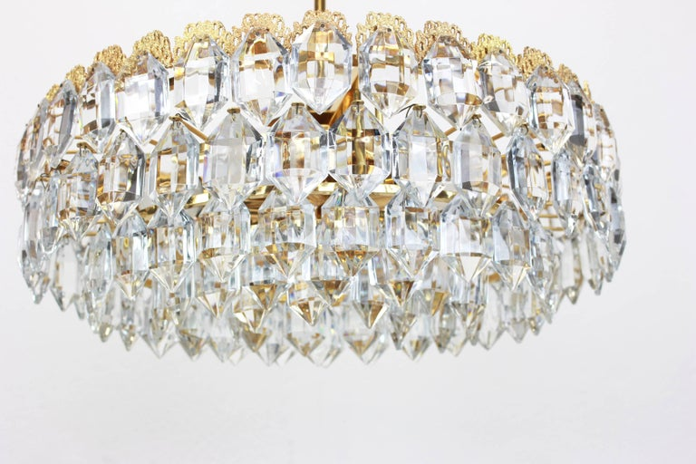A stunning five-tier chandelier by Bakalowits & Sohne, Austria, manufactured in circa 1960-1969. A handmade and high quality piece. The ceiling fixture and the frame are made of gilt brass and have five rings with lots of facetted crystal glass