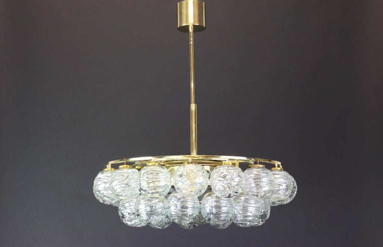 A stunning Mid-Century chandelier made by Doria Leuchtern, manufactured in Germany, circa 1970-1979. The chandelier is composed of 31 glass swirl textured ice glass elements (snowballs) attached to a brass frame. All glass balls are in very good
