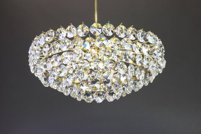 A stunning six-tier chandelier by Bakalowits & Sohne, Austria, manufactured, circa 1960-1969. A handmade and high quality piece. The ceiling fixture and the frame are made of gilt brass and has six rings with lots of facetted crystal glass elements.