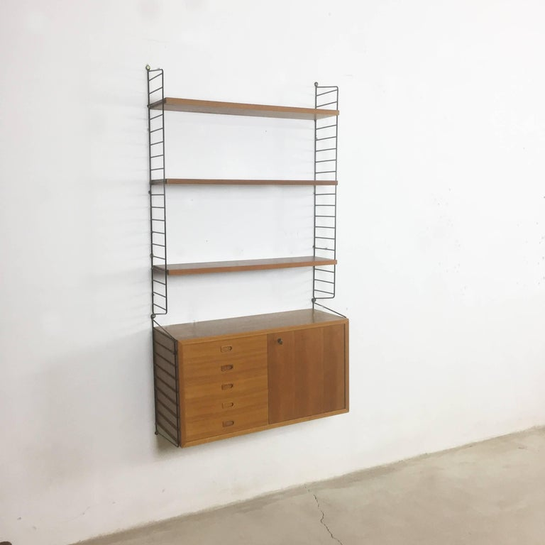String Regal wall unit  Made in Sweden  Bokhyllan 'The Ladder Shelf'  Design: Nils und Kajsa Strinning, 1949  The architect Nisse Strinning was born in 1917. From 1940-1947 he studied architecture in Stockholm, before he designed the