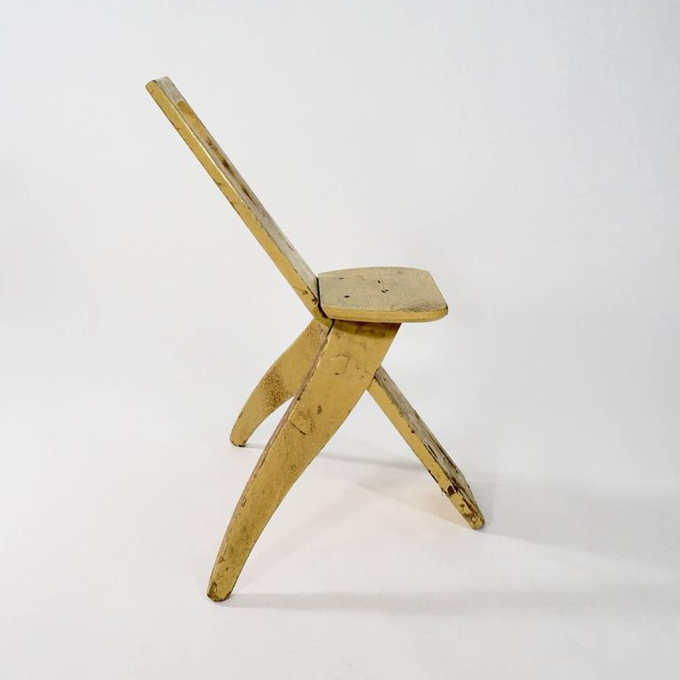 The plank back with a pierced motif with two shaped splaying back legs supporting a simple seat.