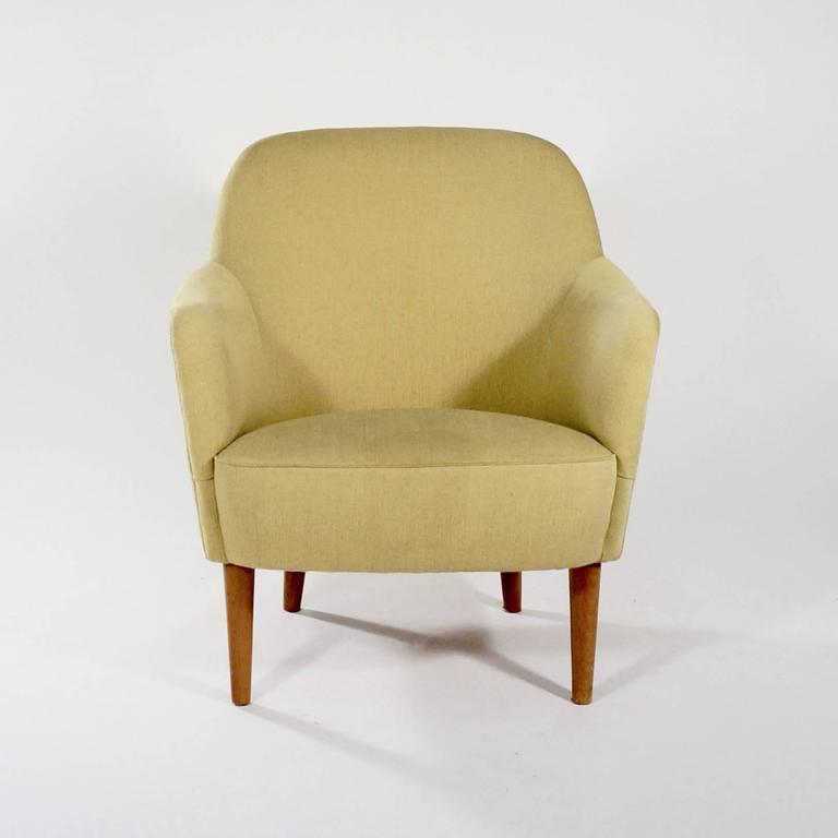 An upholstered 'Sampsel' chair with stained beech legs, a curved back and roll-over arms,