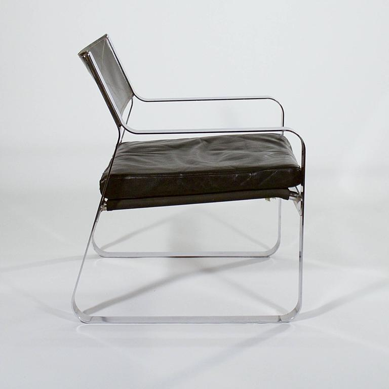 A rare polished steel armchair with a riveted frame and stitched black leather back and seat cushion attributed to Karl Erik Ekselius (1914-1998).  Denmark, circa 1960s.