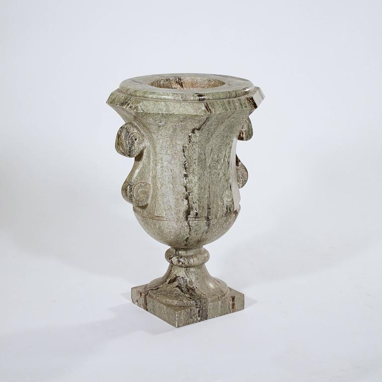 The urn body flanked by scrolling handles above a splaying socle on a square base.