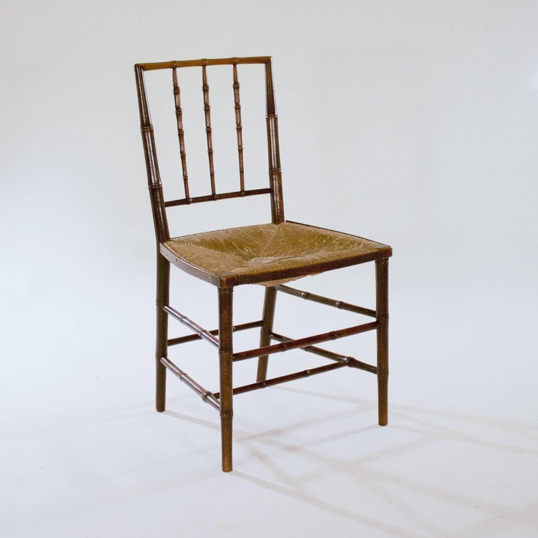 The spindle backs with tapered uprights above the original rush seats supported by tapered legs.