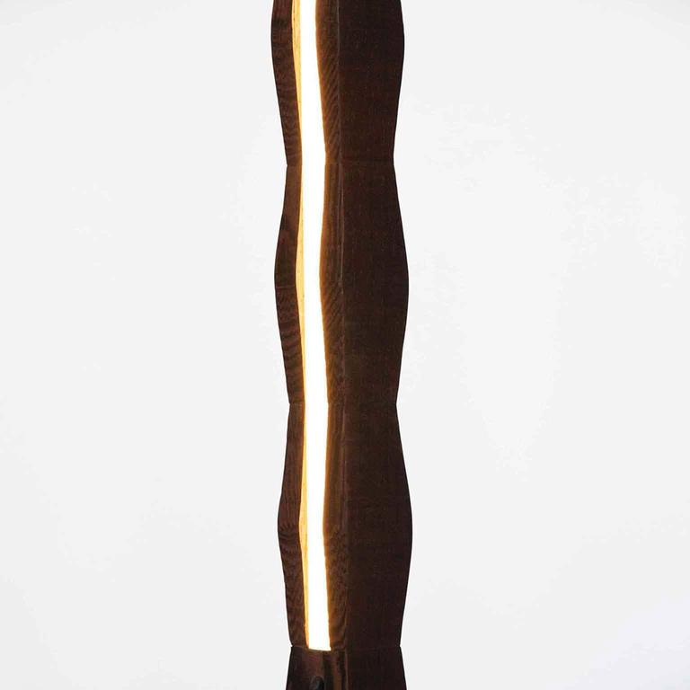 Fort Makers' Column Wenge Line Light is made in Brooklyn by Noah Spencer. This sculptural LED light juxtaposes hard lines with soft reflected light and emits an ambient aura. The lifespan of an LED strip is approximately 50,000 hours. 12 Volts LED
