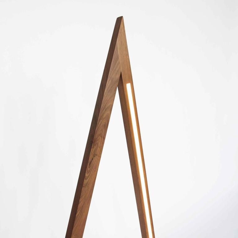 Fort Makers' Tall Skinny Triangle Walnut Line Light is made in Brooklyn by Noah Spencer. This sculptural LED light juxtaposes hard lines with soft reflected light and emits an ambient aura. The lifespan of an LED strip is approximately 50,000