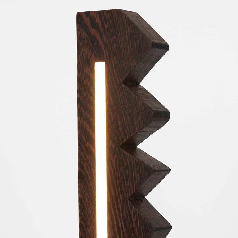 Fort Makers' Chunky Zag Wenge Line Light is made in Brooklyn by Noah Spencer. This sculptural LED light juxtaposes hard lines with soft reflected light and emits an ambient aura. The lifespan of an LED strip is approximately 50,000 hours. 12 Volts