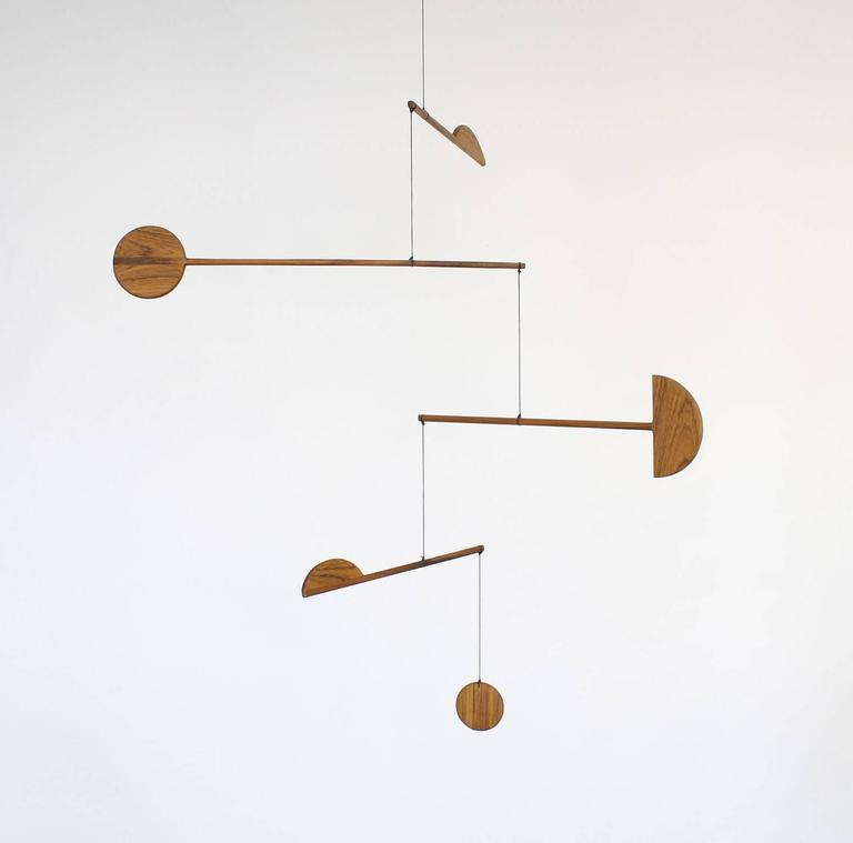 Fort Makers' Paddle Mobile is made in Brooklyn by Noah Spencer. His wooden kinetic sculptures explore organic and linear form and touch upon a human fascination with the universe.  Materials: teak, wax string with end loop for hanging