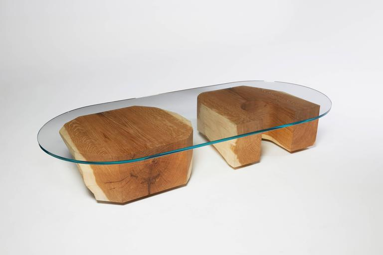 The Tumble Table is a usable sculpture by Noah Spencer made out of two, large, carved pieces of whole white oak and an oval piece of glass. The chunky shapes that hold up the glass tabletop can be placed horizontally on their sides, or vertically