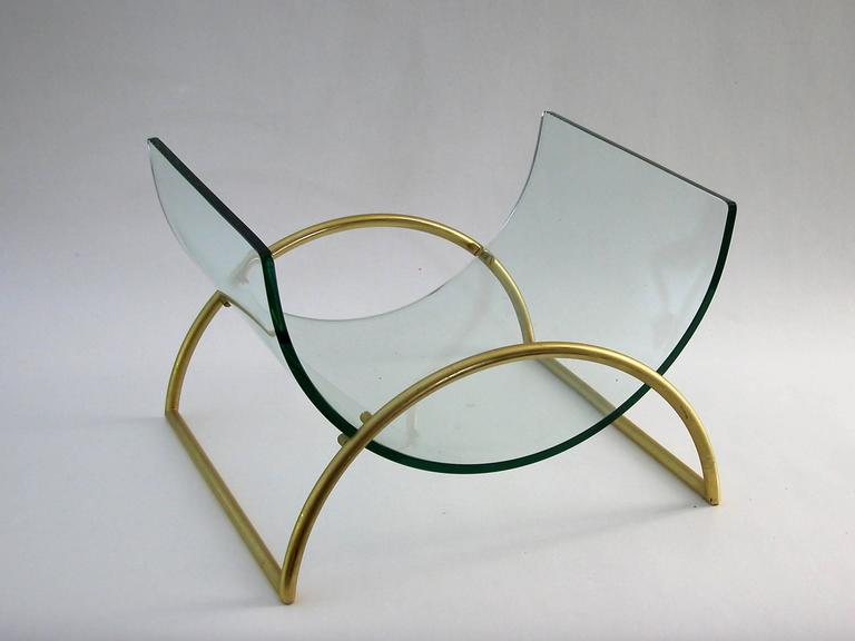 Magazine rack holder by Fontana Arte, circa 1960s. A curved thick glass shelf held within a curved gilded metal holder.