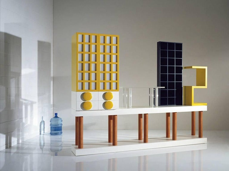 Cabinet consisting of a laminate base with legs one in pear, upper part with two doors in lacquered yellow with frosted glass and four drawers in white lacquered, table in transparent Plexiglas, element in dyed day black and yellow lacquered objects