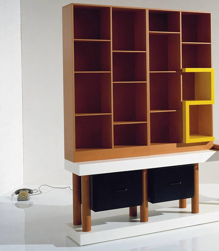 Cabinet consisting of a laminate base with one pear-shaped legs and two black lacquered drawers, upper part with pear-shaped open elements with shelves and yellow lacquered objects and pear-shaped top. Limited edition of 20 copies. Out production.