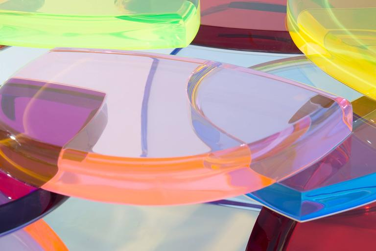 A beautiful coffee table with a structure of colored sequences of plexiglass modules that are repeated by building the shape.