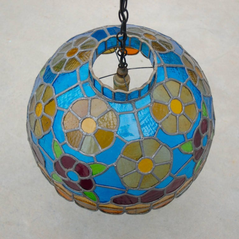 Colorful, completely crafted by hand, handmade stained glass pendant lamp with floral motif and scalloped edge or rim in a style that's commonly referred to as Tiffany although this lamp is by an unknown maker. This lamp has been carefully crafted