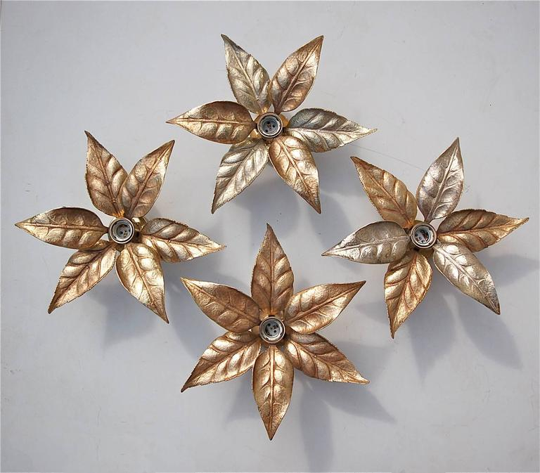 A gold coloured wall sconce or wall light by Belgian designer Willy Daro for lighting manufacturer Massive. It has a wonderful naturalistic shape and is very evocative of the 1970s era. The patina that has built up over the years enhances their warm