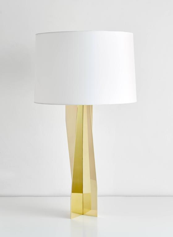 Geometric, reflective, strikingly modern, this made to order brass lamp can be customized in any size finish or material. Shown here in mirror polished finish with a white silk shade.