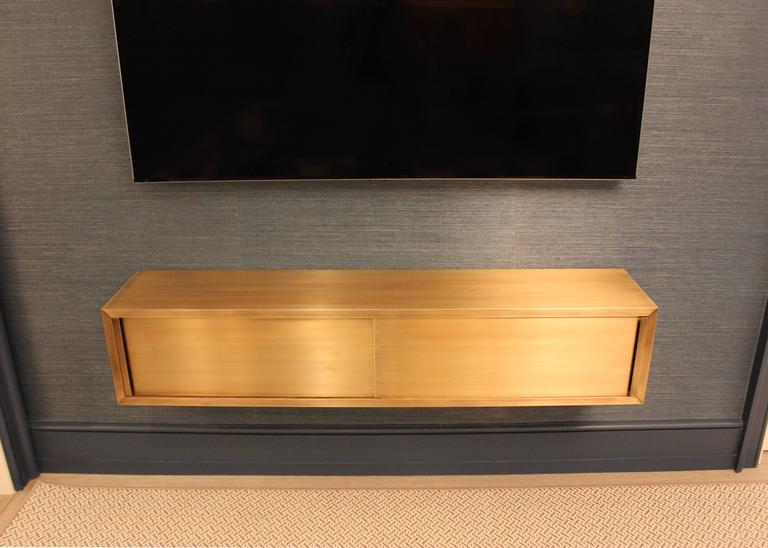 Wall-mounted console in bright satin patinated bronze finish. Stained walnut interior houses media equipment. Available in custom sizes, finishes and materials.