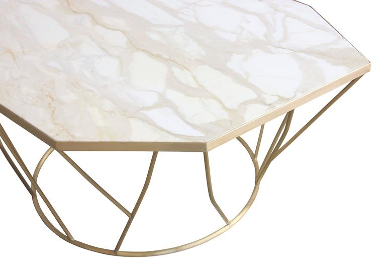 James Devlin Studio's Facet Cocktail Table is a beautiful and sculptural piece comprising a custom shaped marble slab inlaid into a bronze frame atop a hand welded sculptural base. It presents a visually lightweight yet complex and stimulating