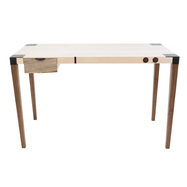 This writer's desk is an exercise in restraint. This sleek desk's tapered legs are made from solid Walnut and are detachable thanks to the custom blackened steel joinery. The solid wood top of this fully customizable piece features inlays and/or