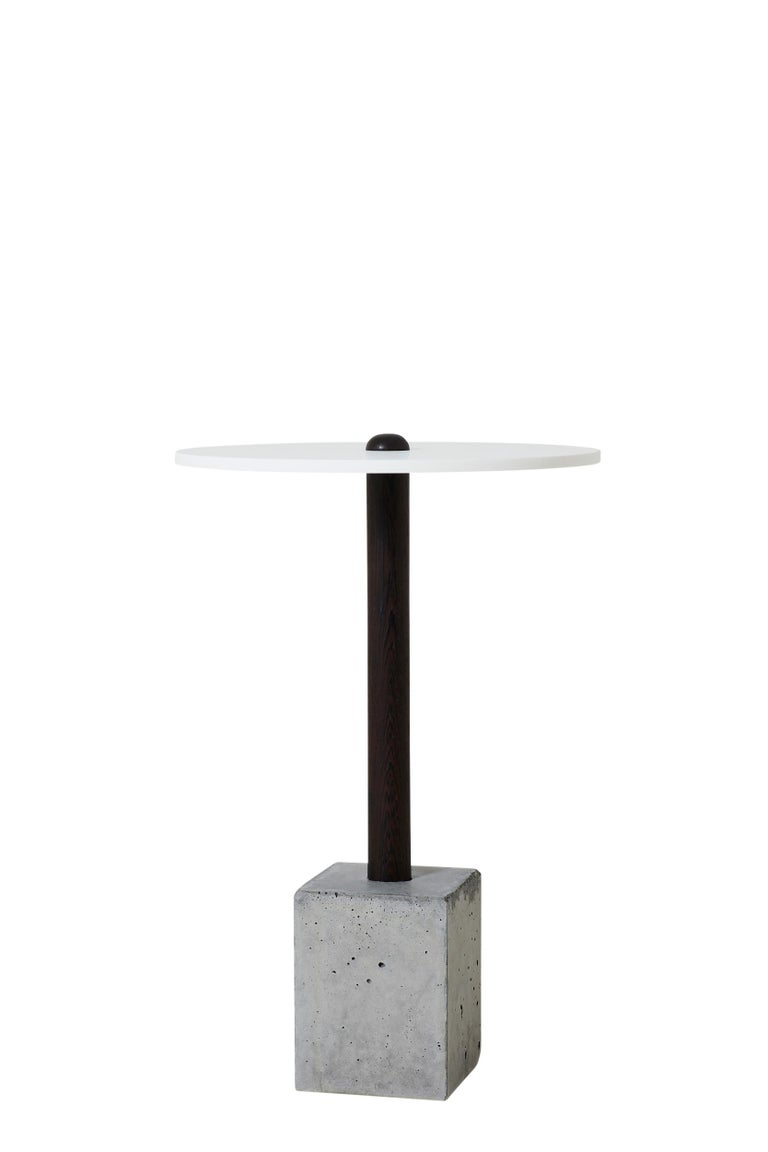 This simple and elegant design is composed of a hand-turned upright piece of wood that is cast into a concrete base. Shown in wenge, the concrete base is either a clean cube or a rougher