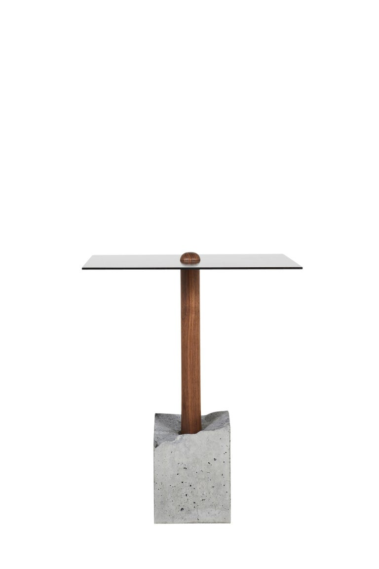 This simple and elegant design is composed of a hand-turned upright piece of wood that is cast into a concrete base. Shown in walnut, the concrete base is a rough