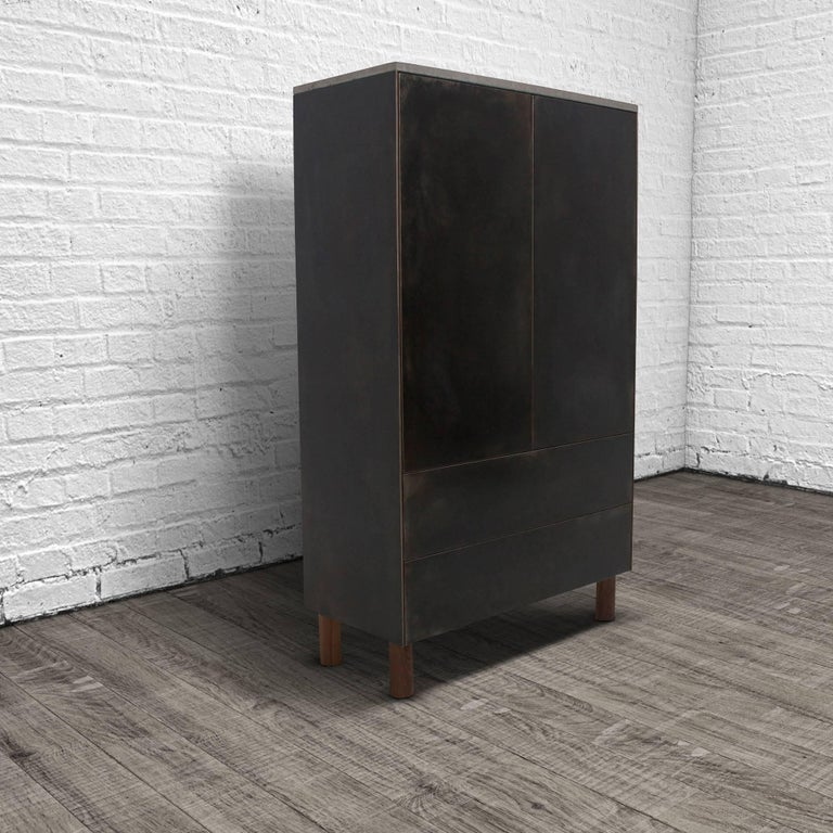 This cabinet combines three elemental materials, concrete, steel and wood to create a grounded, but elegant piece of furniture. The fascia is cold-rolled steel laminated to a walnut veneer core. The cabinet is topped with a cast-concrete slab.