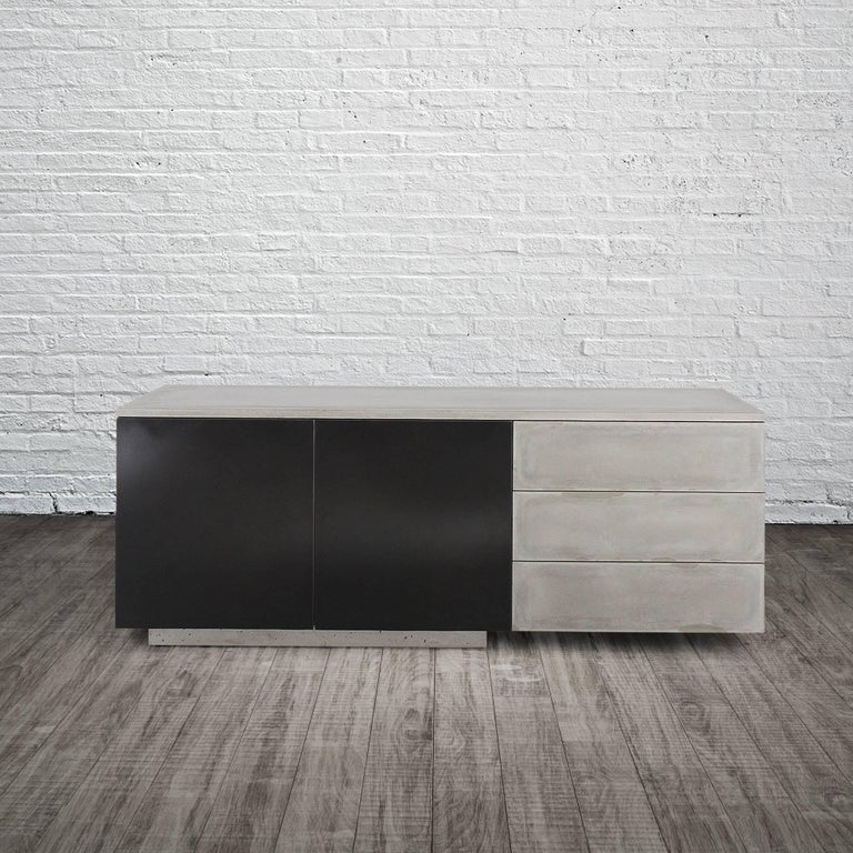 C-210 seamlessly integrates three elemental materials, concrete, steel and wood. The counter-top as well as the drawer faces are all cast concrete. The piece is fully wrapped and fully finished (front and back) with hand-blackened steel that is