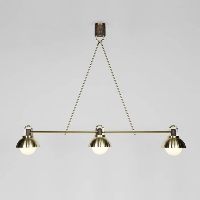 """A contemporary take on a traditional billiard style fixture with meticulously fabricated joinery, bringing together three 10"""" pendants into one linear centerpiece."""