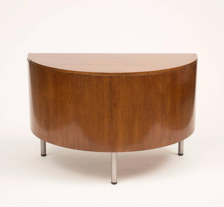An elegant demilune writing desk in walnut by Gilbert Rohde with chrome legs. Designed in 1942 for Herman Miller.