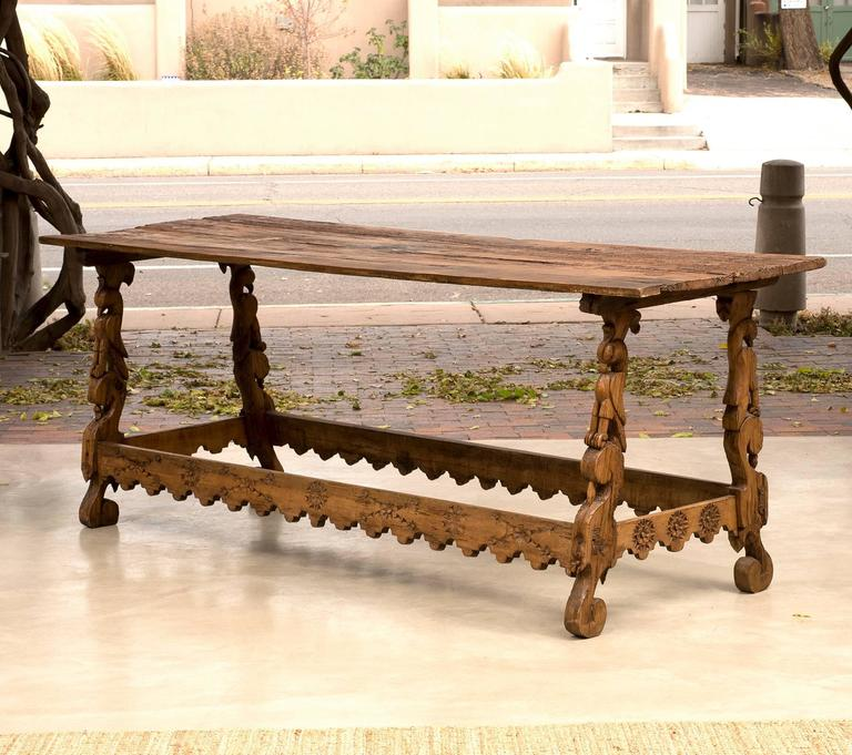 A stunning Spanish Colonial stretcher base table from Mexico in pine with beautiful carved falcon legs, early 18th century.