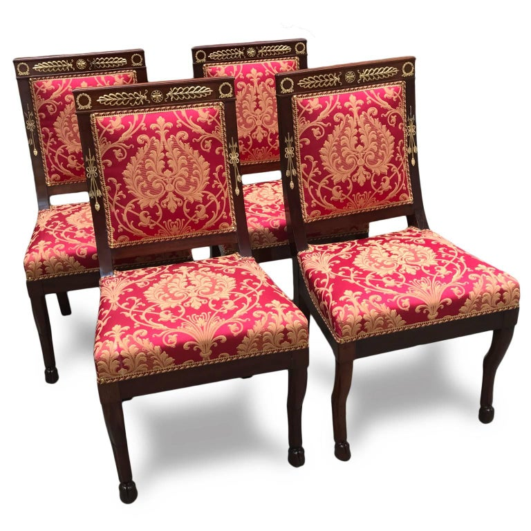 Al set of four solid mahogany chairs in the fabulous Empire style made in Italy in the late 20th century. The mahogany is beautiful in color and has been embellished with striking ormolu mounts typical of the era, finely cast and gilded elaborate