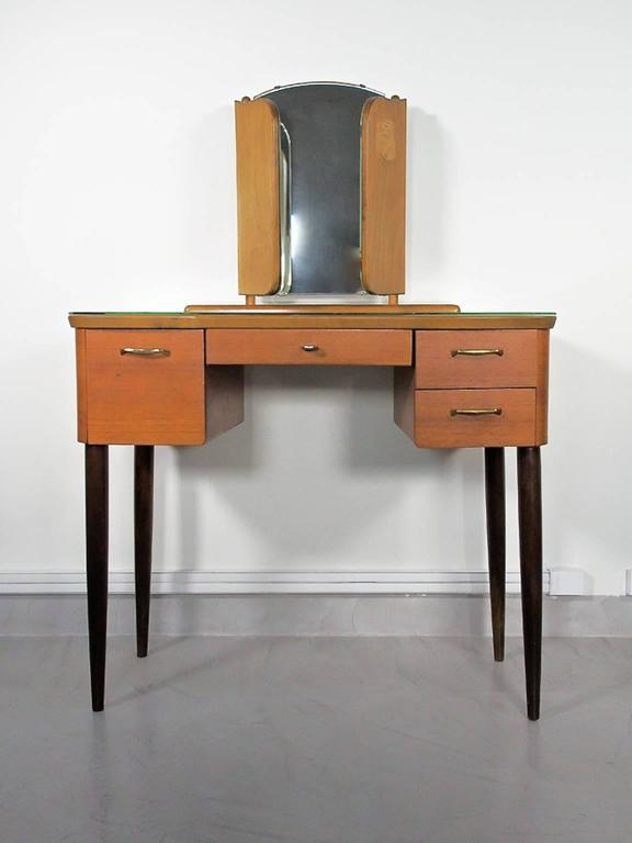 Beautiful Mid-Century Modern teak dressing table with angled mirror and glass top. Drawers in the front. Round stained wood legs. Manufactured in Sweden by Fröseke AB.