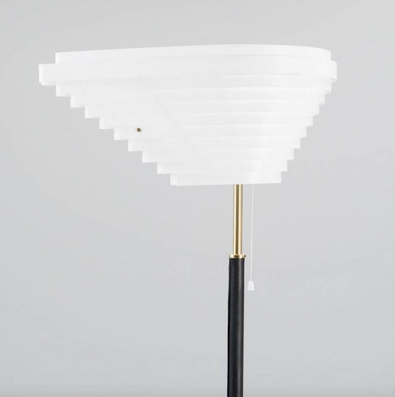 Late 20th century floor lamp Angel Wing, model A805, originally designed by Alvar Aalto in 1954 and later manufactured by Valaisinpaja Oy, Finland. White louvered metal shade. Shaft and base covered with black leather, brass details. Marked with