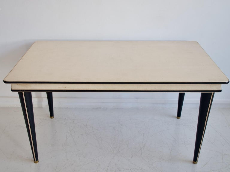 Dining table by Umberto Mascagni, from the Turin series, 1950s. Cream-colored imitation leather tabletop with black trim on the edge. Black conical legs covered in vinyl with inlaid gold metal trim. Some signs of age-related wear.  Set of six
