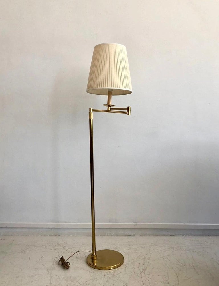 Brass floor lamp in the style of Hans-Agne Jakobsson with adjustable arm and cream-colored shade from circa 1980s. European plug. Great reading lamp due to its adjustable arm, which goes out up to 50 cm.